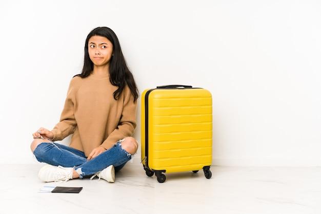 Jonge chinese reizigersvrouw die op de vloer zit met een geïsoleerde koffer, verward, twijfelachtig en onzeker voelt.