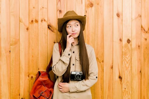 Jonge chinese reizigersvrouw die zijdelings met twijfelachtige en sceptische uitdrukking kijkt.