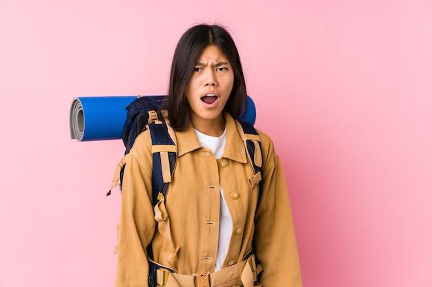 Jonge chinese reizigersvrouw geïsoleerd schreeuwen erg boos en agressief.
