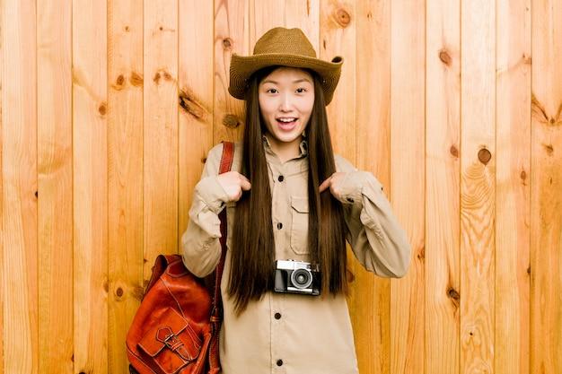 Jonge chinese reizigersvrouw verrast die met vinger richt, breed glimlachend.