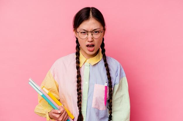 Jonge chinese student vrouw met boeken, gekleed in een mode veelkleurige shirt en vlecht, geïsoleerd op roze achtergrond schreeuwen erg boos en agressief.