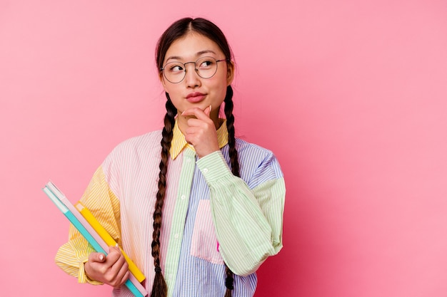 Jonge chinese student vrouw met boeken in een mode veelkleurig shirt en vlecht, geïsoleerd op roze achtergrond zijwaarts kijkend met twijfelachtige en sceptische uitdrukking.