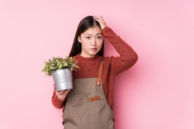Jonge chinese tuinmanvrouw die een installatie geïsoleerd houden geschokt houdt, heeft zij belangrijke vergadering herinnerd.