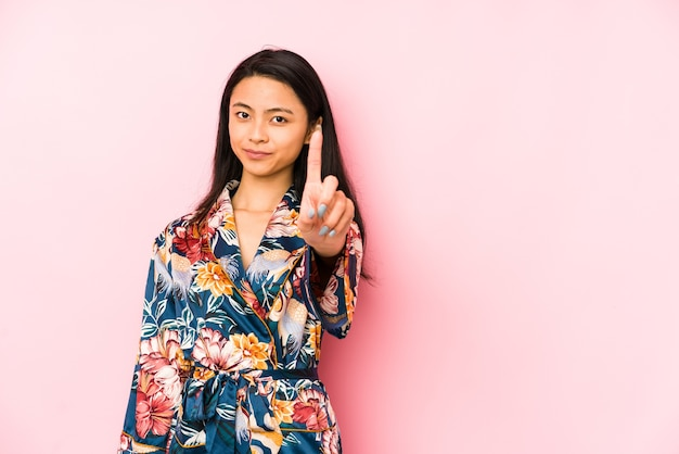 Jonge chinese vrouw die een aziatische geïsoleerde pijama draagt die achterkant van het hoofd raakt, denkt en een keus maakt.