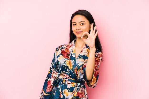 Jonge chinese vrouw die een aziatische pijama draagt die ok teken toont