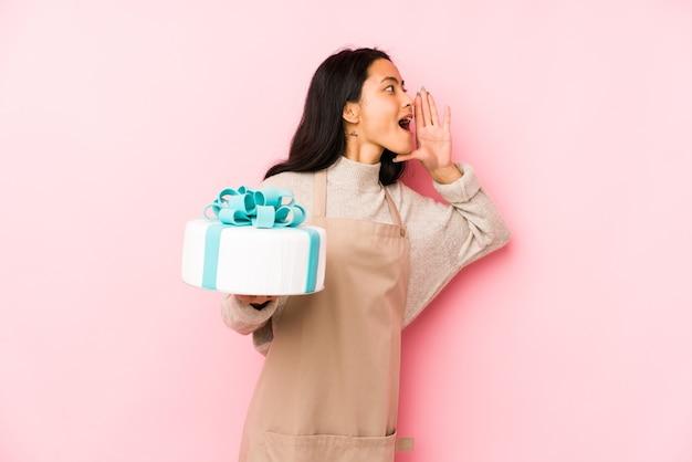 Jonge chinese vrouw die een cake geïsoleerd schreeuwen houdt