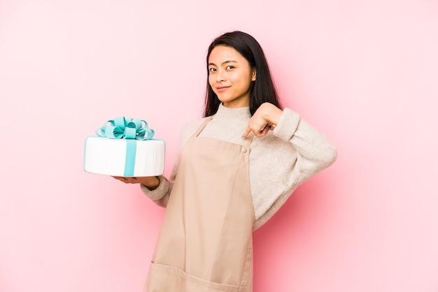 Jonge chinese vrouw die een geïsoleerde cake houdt die van het bereiken van doelstellingen en doeleinden droomt