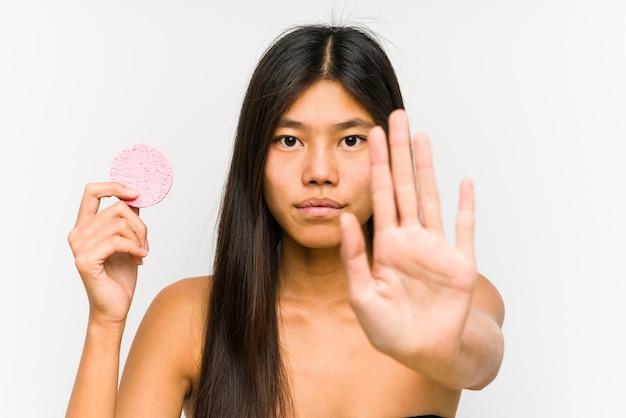 Jonge chinese vrouw die een geïsoleerde gezichtsschijf houdt die zich met uitgestrekte hand bevindt die stopbord toont, dat u verhindert.