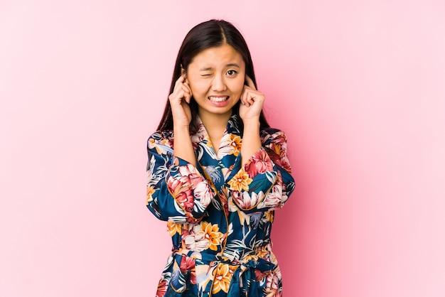 Jonge chinese vrouw die een geïsoleerde kimonopyjama draagt die oren behandelen met handen.