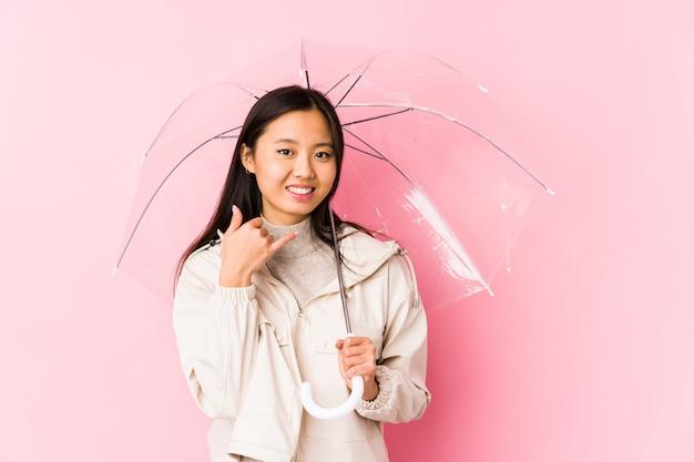 Jonge chinese vrouw die een geïsoleerde paraplu houdt die een mobiel telefoongesprekgebaar met vingers toont.