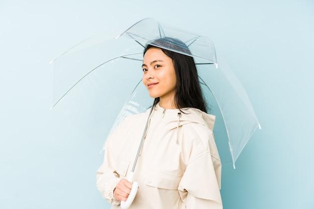 Jonge chinese vrouw die een geïsoleerde paraplu houdt die zijwaarts met twijfelachtige en sceptische uitdrukking kijkt.