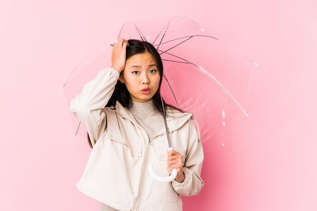 Jonge chinese vrouw die een geïsoleerde paraplu houdt wordt geschokt, heeft zij belangrijke vergadering herinnerd.