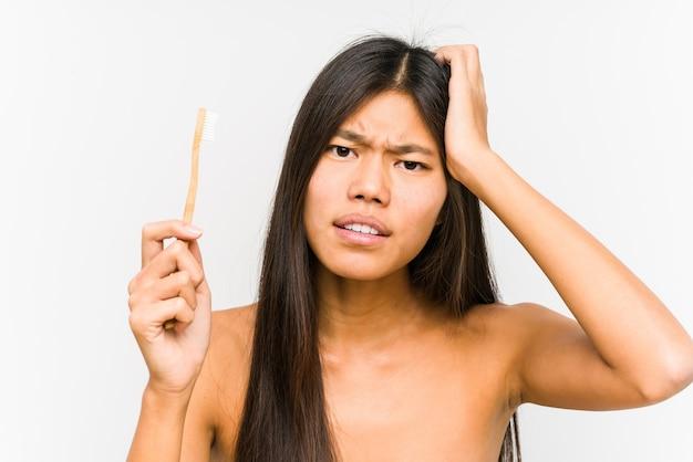 Jonge chinese vrouw die een geïsoleerde tandenborstel houdt die geschokt is, heeft zij belangrijke vergadering herinnerd.