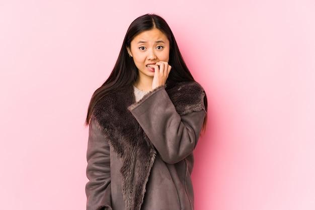 Jonge chinese vrouw die een jas draagt geïsoleerd bijtende vingernagels, zenuwachtig en zeer angstig.