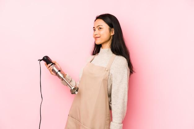Jonge chinese vrouw die een mixer geïsoleerd houdt zijwaarts kijkend met twijfelachtige en sceptische uitdrukking.