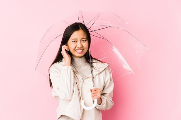 Jonge chinese vrouw die een paraplu geïsoleerd houdt behandelend oren met handen.