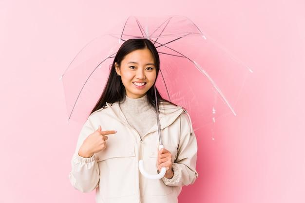 Jonge chinese vrouw die een paraplupersoon houdt die met de hand aan zich richt