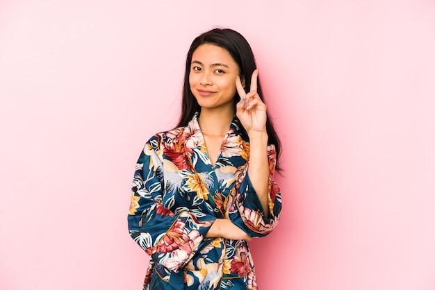 Jonge chinese vrouw die een pijama draagt die met vingers op lippen wordt geïsoleerd die een geheim houden.