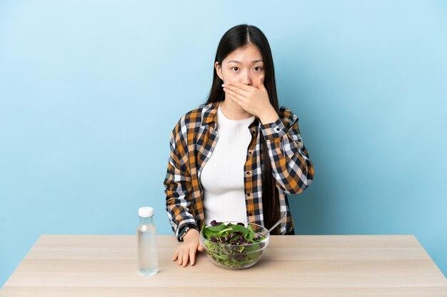 Jonge chinese vrouw die een salade eet die mond behandelt met hand