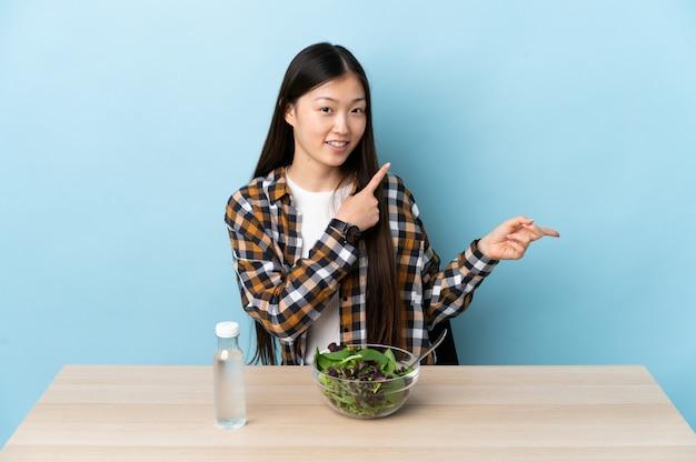 Jonge chinese vrouw die een salade eet die vinger aan de kant richt en een product voorstelt