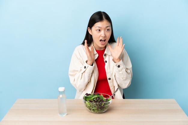 Jonge chinese vrouw die een salade met verrassingsgelaatsuitdrukking eet