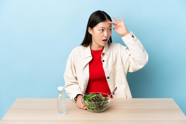 Jonge chinese vrouw die een salade met verrassingsuitdrukking eet terwijl het kijken kant