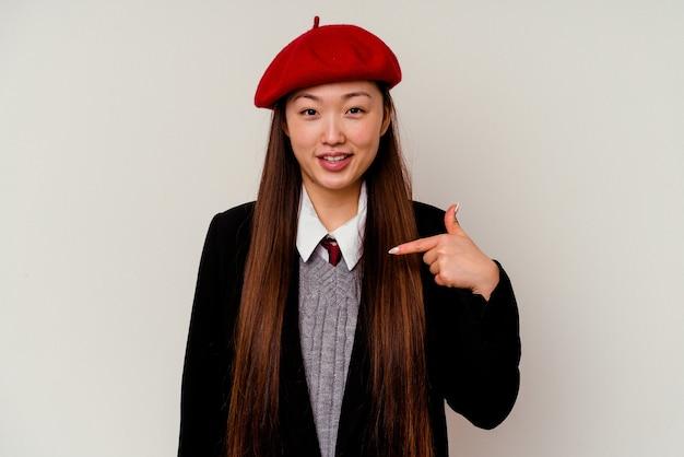 Jonge chinese vrouw die een school eenvormige persoon draagt die met de hand naar een overhemds exemplaarruimte richt, trots en zelfverzekerd