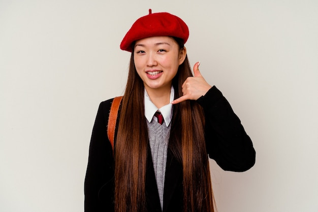 Jonge chinese vrouw die een schooluniform draagt dat op witte achtergrond wordt geïsoleerd die een mobiel telefoongesprekgebaar met vingers toont.