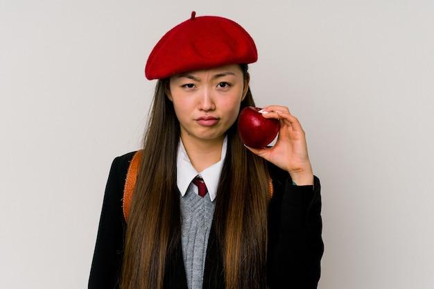 Jonge chinese vrouw die een schooluniform draagt die op witte achtergrond wordt geïsoleerd