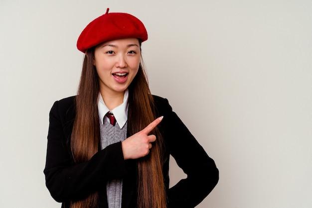 Jonge chinese vrouw die een schooluniform draagt en opzij glimlacht wijst, iets toont