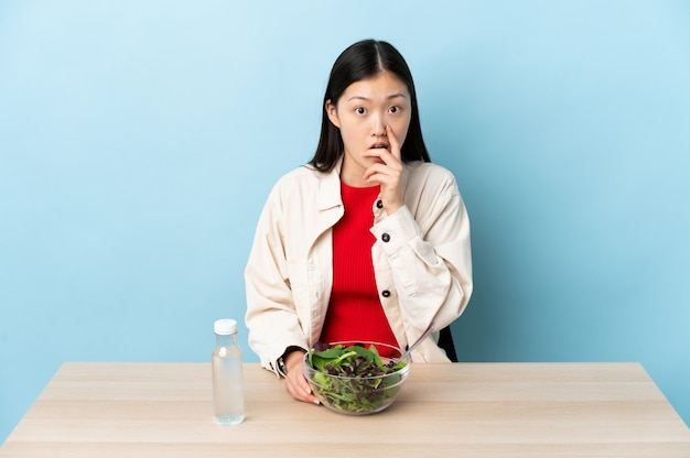 Jonge chinese vrouw die een verraste en geschokte salade eet terwijl net het kijken