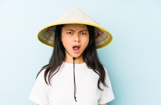 Jonge chinese vrouw die een vietnamees geïsoleerd hooi draagt, blij en zorgeloos met een vredessymbool met vingers.
