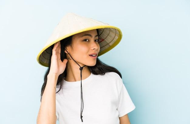 Jonge chinese vrouw die een vietnamees hooi draagt, is geschokt en herinnert zich een belangrijke bijeenkomst.