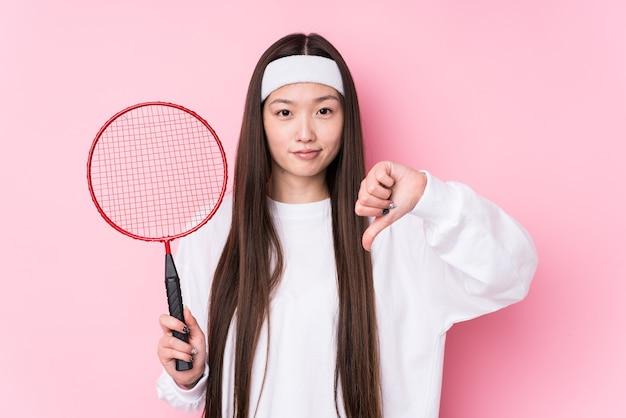 Jonge chinese vrouw die geïsoleerd badminton speelt met een afkeergebaar, duimen naar beneden. meningsverschil concept.