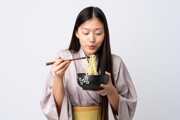 Jonge chinese vrouw die kimono over geïsoleerde witte muur draagt die een kom van noedels met eetstokjezand houdt die het blaast omdat zij heet zijn