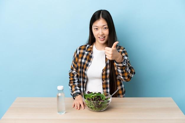 Jonge chinese vrouw die met duimen omhoog een salade eet omdat er iets goeds is gebeurd