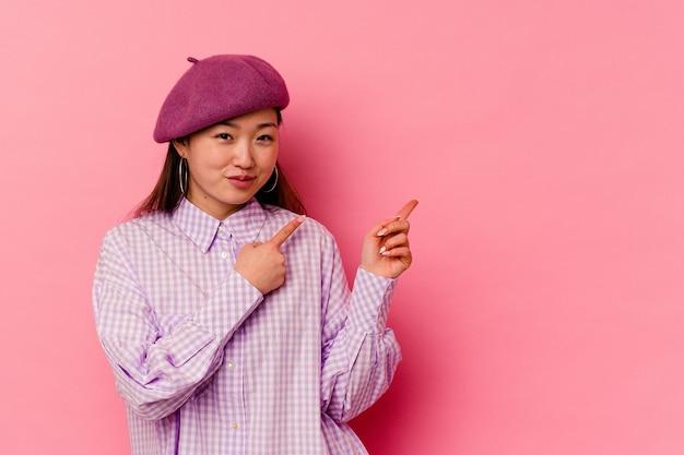 Jonge chinese vrouw die met wijsvingers naar een exemplaarruimte richt, opwinding en verlangen uitdrukt.