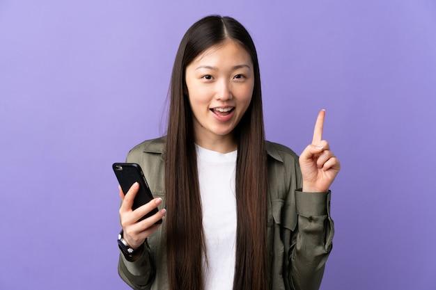 Jonge chinese vrouw die mobiele telefoon over geïsoleerde purpere muur met behulp van die een groot idee benadrukken