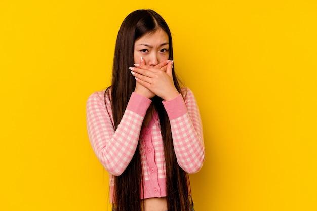 Jonge chinese vrouw die mond behandelt met handen die ongerust kijken.