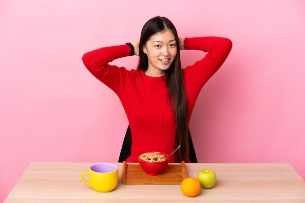 Jonge chinese vrouw die ontbijt in lijst het lachen heeft