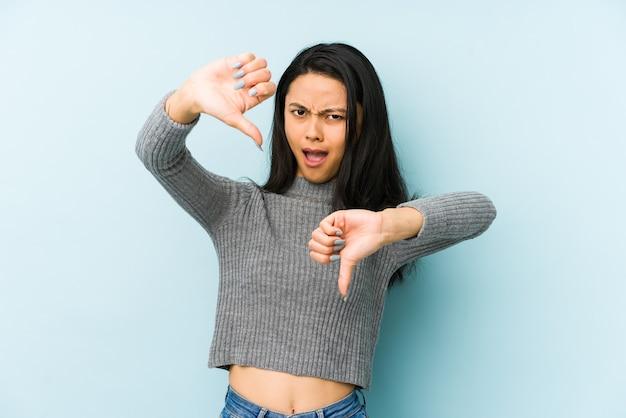 Jonge chinese vrouw die op een blauwe muur wordt geïsoleerd die duim neer toont en afkeer uitdrukt.