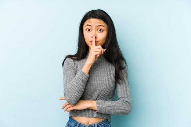 Jonge chinese vrouw die op een blauwe muur wordt geïsoleerd die een geheim houdt of om stilte vraagt.