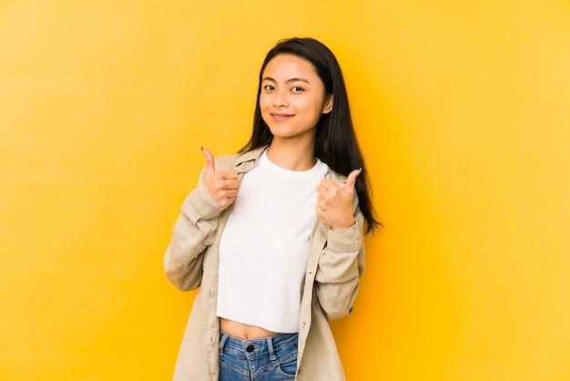 Jonge chinese vrouw die op een gele muur wordt geïsoleerd die beide duimen opheft, glimlachend en zelfverzekerd.
