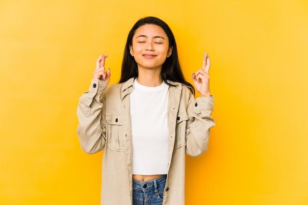 Jonge chinese vrouw die op een gele muur wordt geïsoleerd die vingers kruist voor het hebben van geluk