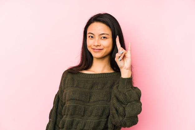 Jonge chinese vrouw die op een roze muur wordt geïsoleerd die een hoornsgebaar toont als revolutieconcept
