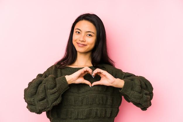Jonge chinese vrouw die op een roze muur wordt geïsoleerd die en een hartvorm met handen glimlacht toont.