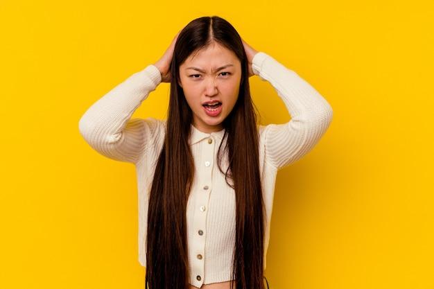 Jonge chinese vrouw die op gele achtergrond wordt geïsoleerd die van woede schreeuwt.