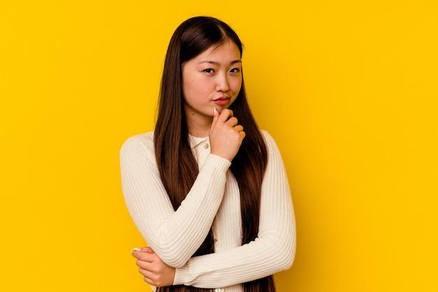 Jonge chinese vrouw die op gele muur verdacht, onzeker wordt geïsoleerd, die u onderzoekt