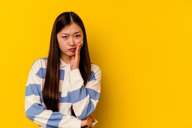 Jonge chinese vrouw die op gele muur wordt geïsoleerd die verdrietig en peinzend voelt, exemplaarruimte bekijkt.