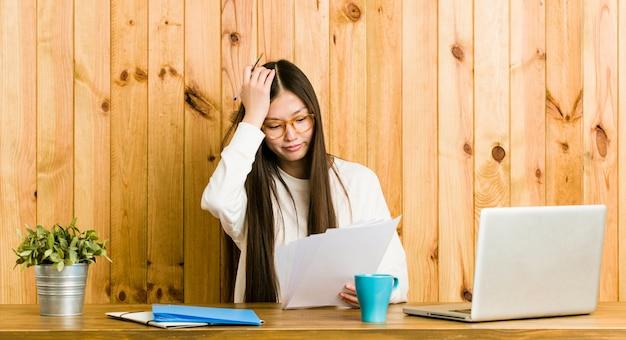 Jonge chinese vrouw die op haar bureau bestudeert dat iets vergeet, voorhoofd met palm mept en ogen sluit.